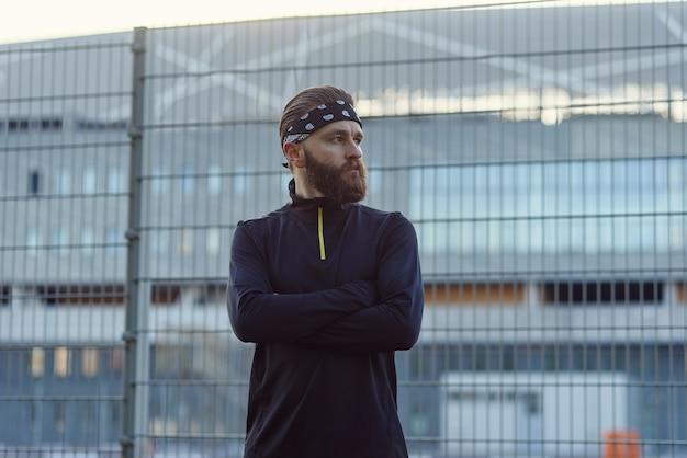 Männlicher bärtiger athlet in sportuniform und bandana nach hartem training auf dem spielplatz