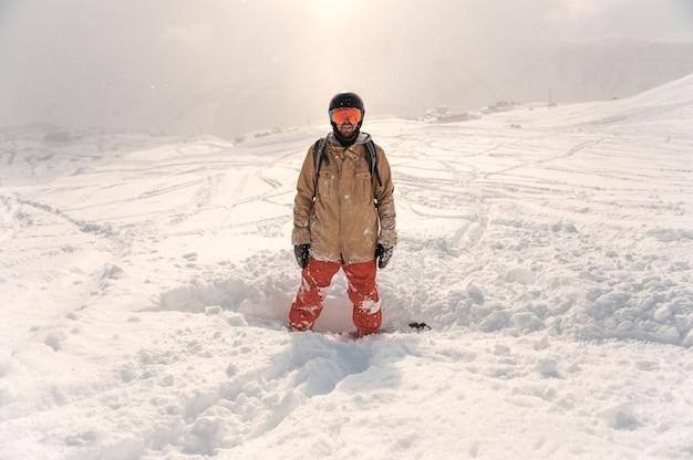 Männlicher bärtiger snowboarder in der sportkleidung und in sturzhelm, die auf dem schneehügel stehen