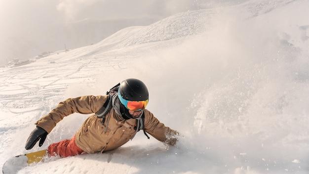Männlicher bärtiger snowboarder in der sportkleidung und in sturzhelm, die hinunter den pulverschneehügel reiten