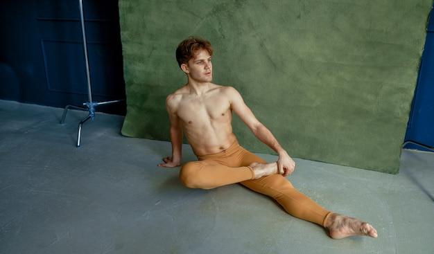 Männlicher balletttänzer, der im tanzunterricht auf dem boden sitzt, grunge-wand im hintergrund