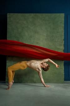 Männlicher balletttänzer, der übung im tanzstudio, in der schmutzwand und im roten tuch tut. performer mit muskulösem körper, anmut und eleganz der bewegungen