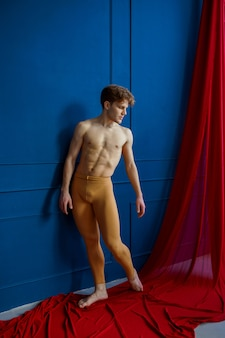 Männlicher balletttänzer, gleichgewichtsübung im tanzstudio, blaue wände und rotes tuch. performer mit muskulösem körper, anmut und eleganz der bewegungen