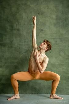 Männlicher balletttänzer posiert an der grunge-wand im tanzstudio