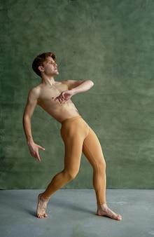 Männlicher balletttänzer, training im tanzunterricht, grunge-wand im hintergrund