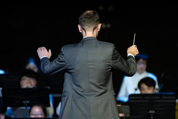 Männlicher banddirigent, der seine blasorchester dirigiert