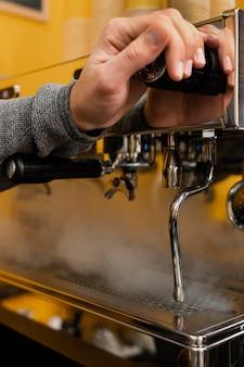 Männlicher barista, der auf professionelle kaffeemaschine einlocht