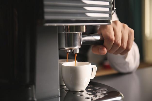 Männlicher barista, der frischen espresso in der kaffeemaschine macht, nah oben