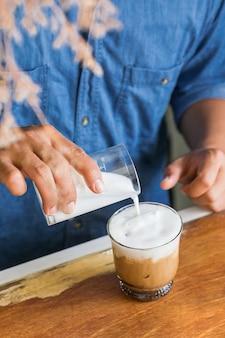 Männlicher barista, der frischen milchschaum auf eiskaffee gießt, um einen gefrorenen latte an der hölzernen thekenbar zu machen.