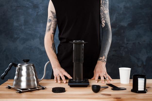 Männlicher barista, der kaffee braut. alternative methode aeropresse.
