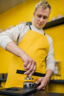 Männlicher barista, der kaffee für maschine verpackt