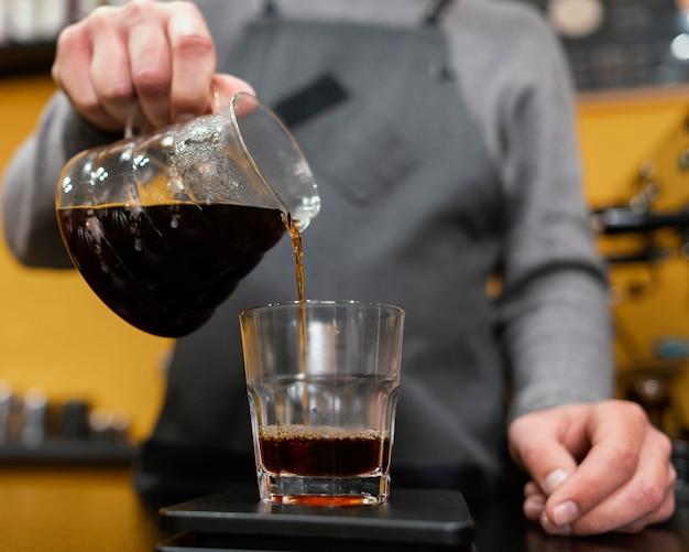 Männlicher barista, der kaffee in transparentem glas gießt