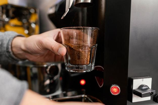 Männlicher barista, der kaffee mit maschine mahlt