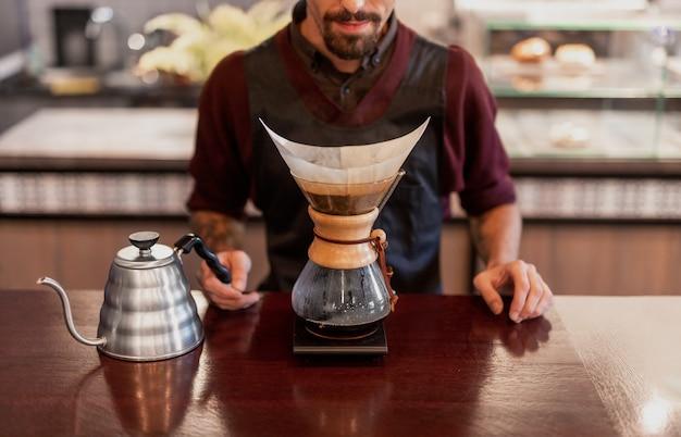 Männlicher barista, der tropfkaffee braut