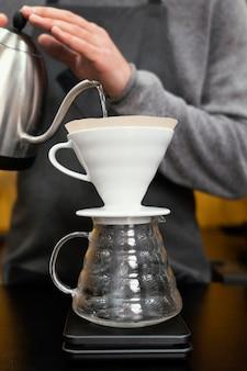 Männlicher barista, der wasser in kaffeefilter gießt
