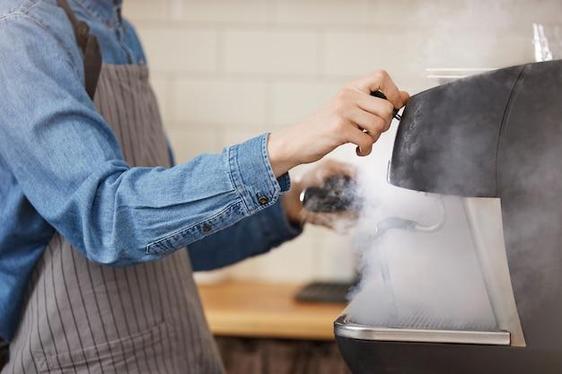 Männlicher barista im einheitlichen waschen der braugeräte unter verwendung des dampfers.
