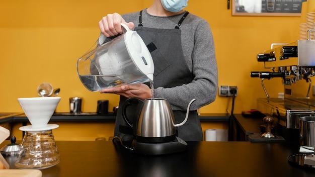 Männlicher barista mit medizinischer maske, die wasser in den kessel gießt