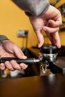 Männlicher barista mit professioneller kaffeemaschinenschale