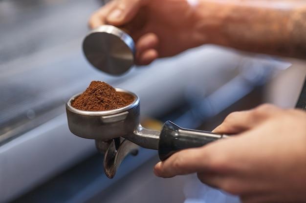 Männlicher barista mit sabotage und siebträger, der gemahlenen kaffee drückt