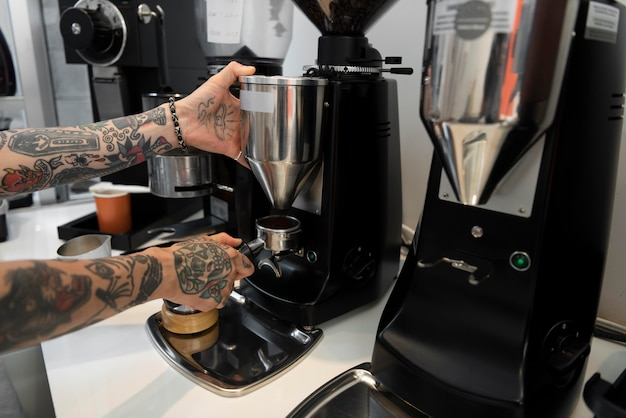 Männlicher barista mit tätowierungen an der kaffeemaschine im café