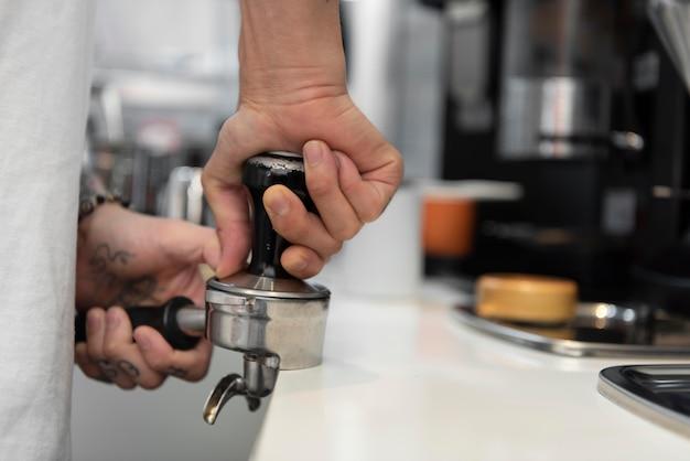 Männlicher barista mit tätowierungen, der kaffee für die kaffeemaschine zubereitet