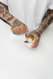 Männlicher barista mit tätowierungen, die milch in kaffeetasse gießen
