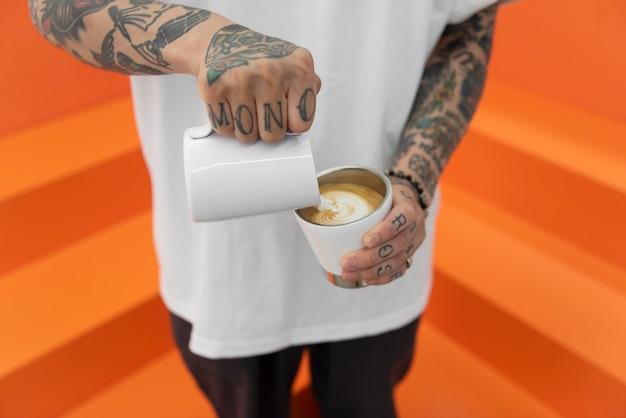 Männlicher barista mit tätowierungen, die milch zum kaffee hinzufügen