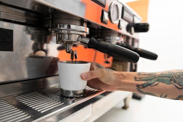Männlicher barista mit tattoos bei der arbeit an der kaffeemaschine
