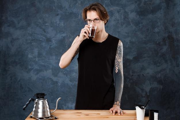 Männlicher barista schmeckt kaffee. alternative brauverfahren.