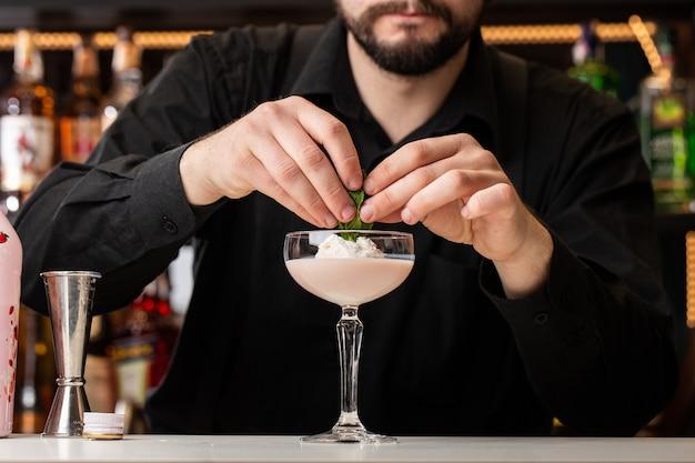 Männlicher barkeeper dekoriert cocktail mit eis und baileys im glas auf der theke