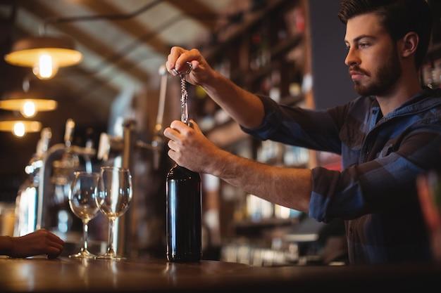 Männlicher barkeeper, der eine flasche wein öffnet