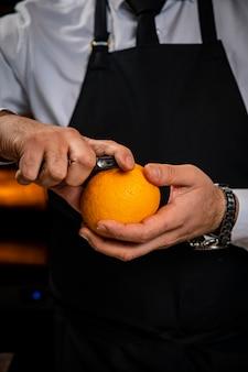 Männlicher barkeeper, der eine orange schält