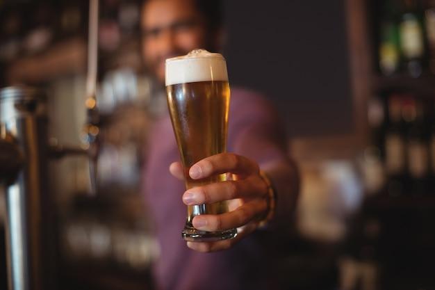 Männlicher barkeeper, der glas bier gibt