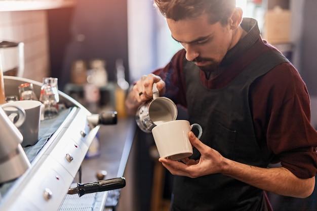 Männlicher barkeeper, der milch in tasse mit kaffee hinzufügt