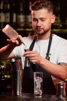 Männlicher barkeeper macht einen cocktail mit einem shaker