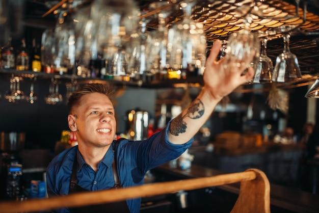 Männlicher barkeeper nimmt sauberes glas von der bartheke