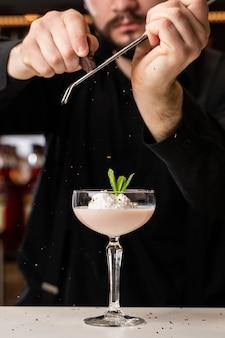 Männlicher barkeeper reibt schokolade mit einer reibe auf einen cocktail mit eis und baileys in einem glas