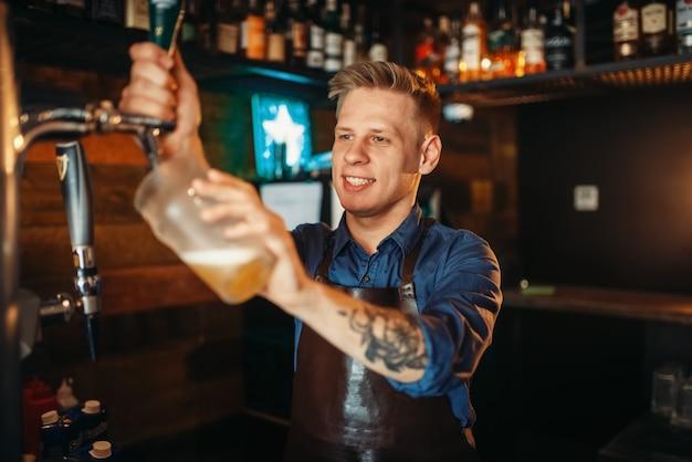 Männlicher barmann, der bier an der bartheke gießt