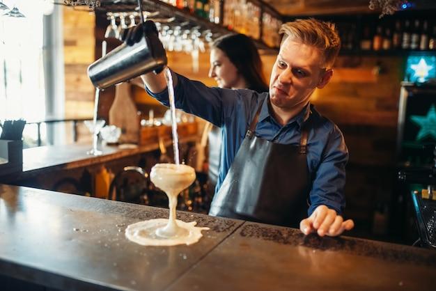 Männlicher barmann, der das getränk vom schüttler einschenkt