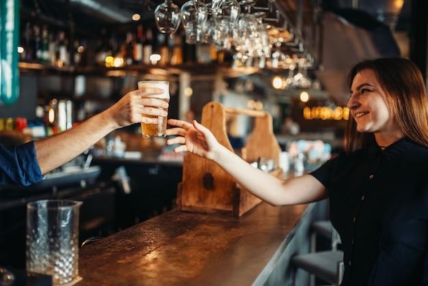 Männlicher barmann gibt dem weiblichen besucher ein glas bier