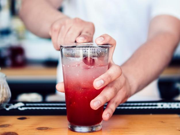 Männlicher barmixer, der cocktailsieb verwendet