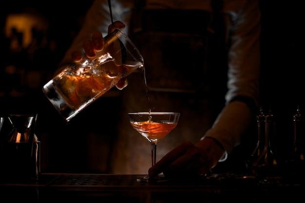 Männlicher barmixer, der ein braunes alkoholisches cocktail vom messbecher zum glas in der dunkelheit gießt