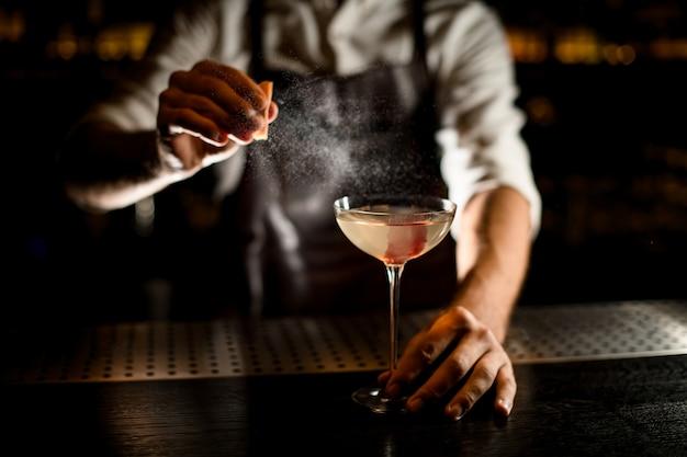 Männlicher barmixer, der ein cocktail im glas verziert mit rosa eiswürfel dient