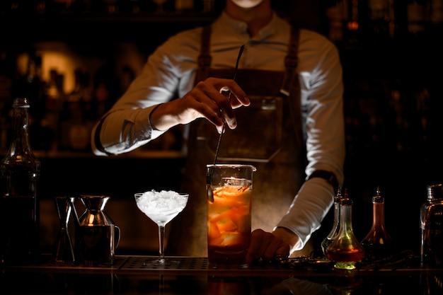 Männlicher barmixer, der ein cocktail in der messenden glasschale rührt