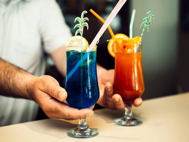 Männlicher barmixer, der exotische cocktails dient