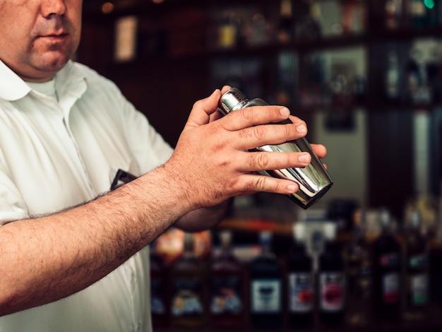 Männlicher barmixer, der getränk im schüttel-apparat vorbereitet