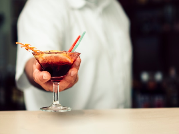 Männlicher barmixer, der vibrierendes getränk im martini-glas dient