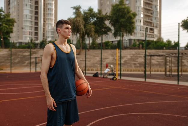 Männlicher basketballspieler hält einen ball auf dem außenplatz.
