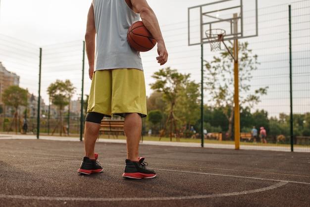 Männlicher basketballspieler mit ball, der am korb auf außenplatz, rückansicht steht.