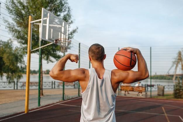 Männlicher basketballspieler mit ball zeigt seine muskeln