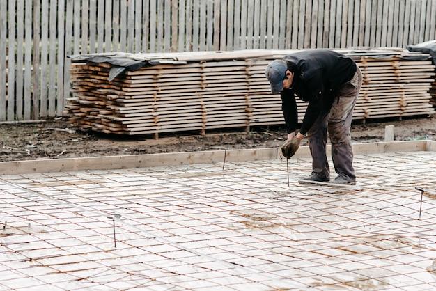Männlicher bauarbeiter bereitet bewehrung für die gründung eines hauses zum betonieren vor